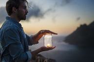 Side view of man holding tea light candle in jar by sea during sunset - CAVF33642