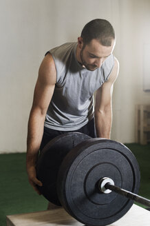 Male athlete fixing barbell in gym - CAVF33696