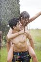 Happy man piggybacking woman while enjoying water spray at yard - CAVF33717