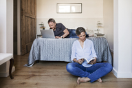 Senior couple using laptop and reading book in bedroom - CAVF33729