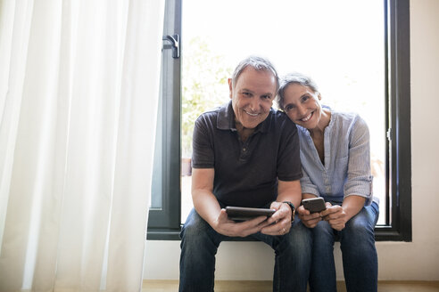 Portrait of happy senior couple holding smart phone and tablet computer while sitting on window sill at home - CAVF33741
