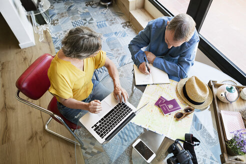 Overhead view of senior couple planning vacation at home - CAVF33744