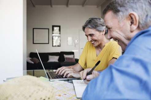 Cheerful senior couple using laptop while planning vacation at home - CAVF33747