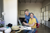 Portrait of happy senior couple planning vacation at home - CAVF33750