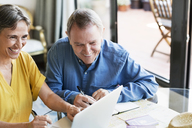 Cheerful senior couple using laptop while planning vacation at home - CAVF33753