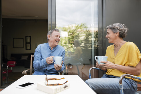 Happy senior couple having coffee at porch - CAVF33774