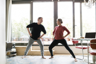 Happy senior couple exercising by window at home - CAVF33786