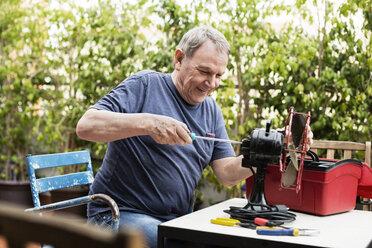 Happy senior man repairing electric fan at yard - CAVF33828