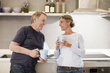 Cheerful senior couple talking while holding coffee mugs in kitchen - CAVF33837