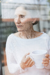 Thoughtful mature woman looking through window while holding coffee mug at home - CAVF33843