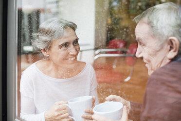 Happy senior couple talking while holding coffee mugs seen through glass window - CAVF33846