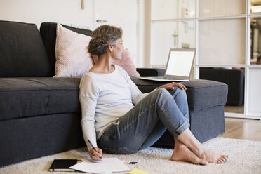 Mature woman writing while using laptop in living room - CAVF33849