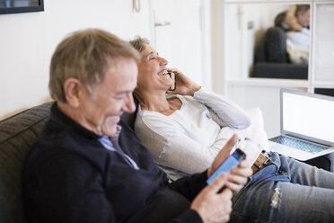 Happy senior couple using smart phones in living room - CAVF33852