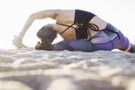 Rear view of woman doing yoga on beach during summer - CAVF33858