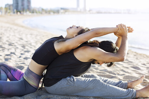 Side view of couple doing yoga together on beach - CAVF33861