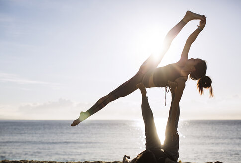 Man lifting woman while performing yoga on beach against sky - CAVF33864