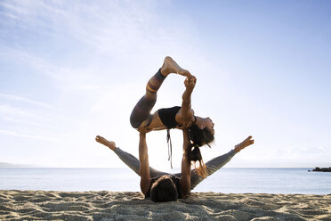 Determined couple doing yoga on shore against sky - CAVF33867