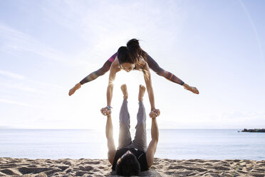 Man lifting woman while doing yoga on beach during summer - CAVF33870