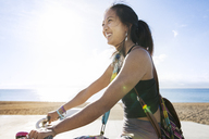 Side view of happy sporty woman riding bicycle by beach - CAVF33879