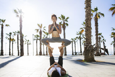 Couple performing yoga on footpath at beach during summer - CAVF33882