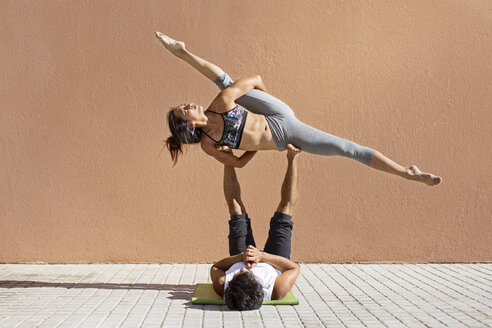 Man lifting woman while doing yoga on sidewalk - CAVF33888