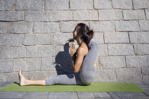 Side view of flexible woman doing yoga on sidewalk against stone wall - CAVF33891
