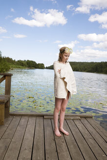 Girl wrapped in towel standing on wooden jetty after swimming - FOLF07960