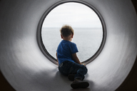 Back view of boy looking through window at Baltic Sea - FOLF08008