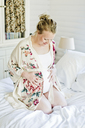 Pregnant mid-adult woman sitting on bed - FOLF08409