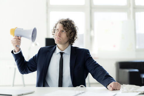 Businessman sitting in office trying out megaphone - HHLMF00159