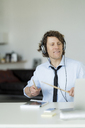 Businessman wearing headphones and drumming on his desk - HHLMF00186