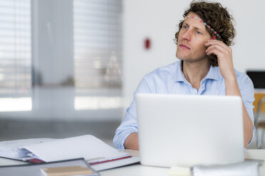 Businessman with headband dreaming at his desk - HHLMF00207