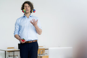 Smiling businessman juggling balls in his office - HHLMF00213