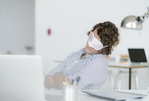 Overworked businessman sleeping at his desk wearing a sleeping mask - HHLMF00219