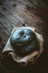 Green pumpkin on jute and dark wood - GIOF03886