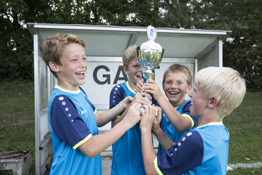 Young football players cheering with cup - WESTF24032