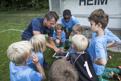 Coach with tablet and young football players on football ground - WESTF24038