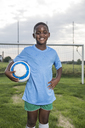 Portrait of smiling young football player holding ball on football ground - WESTF24041