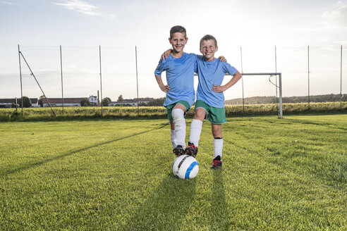 Smiling young football players embracing on football ground - WESTF24044