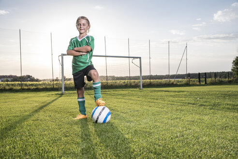Portrait of confident young football player with ball on football ground - WESTF24047