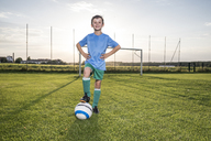 Portrait of confident young football player with ball on football ground - WESTF24050