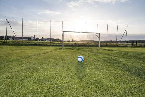 Ball lying on football ground at sunset - WESTF24053