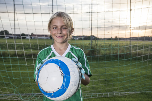 Portrait of smiling young football goalkeeper holding ball on football ground - WESTF24056