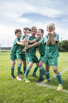 Germany, young football players cheering with cup - WEST24072
