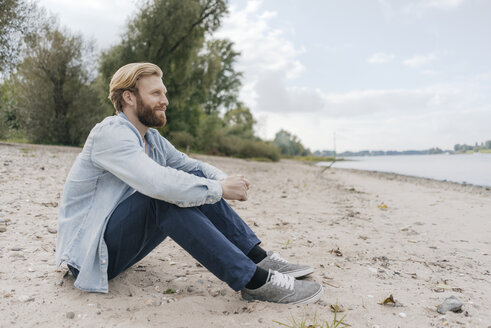 Germany, Duesseldorf, relaxed man sitting on the beach looking at view - KNSF03657