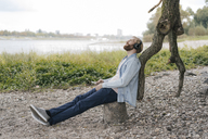 Germany, Duesseldorf, man with smartphone and headphones listening music in nature - KNSF03660