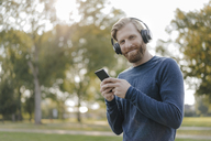 Portrait of smiling man with cell phone listening music with headphones in a park - KNSF03681