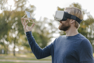 Man in autumnal park wearing Virtual Reality Glasses looking at miniature beach lounger - KNSF03684