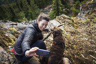 High angle view of woman clicking selfie with dog on mountain cliff - CAVF34001