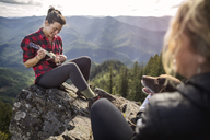 Woman playing ukelele on rock at mountain cliff - CAVF34004